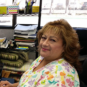 Gina, Medical Assistant, at her desk